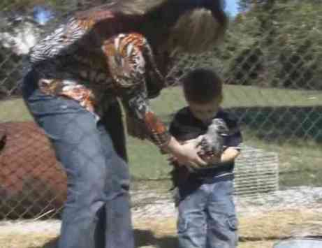 Mom helps JJ get settled to cuddle a chicken (You Tube Image)