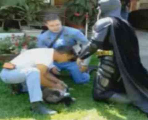 Batman and Others Helping a Cat Rescued from a Burning House (You Tube Image)
