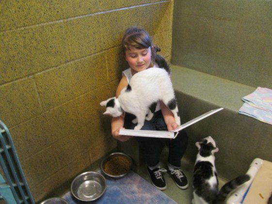 Cassandra, one of the Book Buddies, and furry friends (Photo via Facebook)