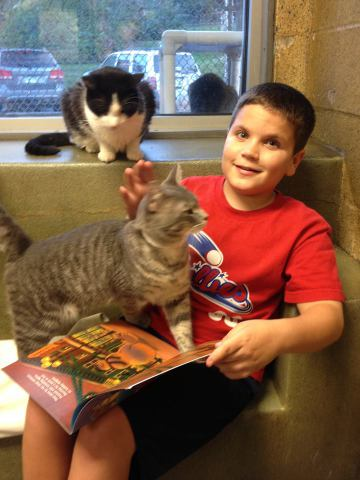 Aidan, one of the Book Buddies, and furry friend (Photo via Facebook)