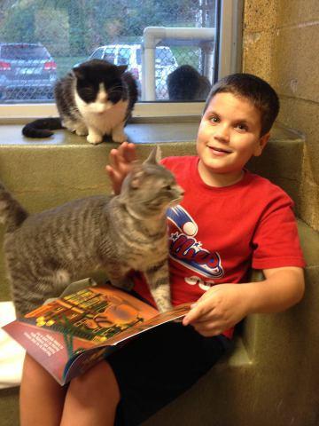 Aidan, one of the Book Buddies, and furry friend (Photo via Facebook)