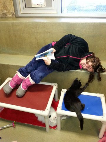 Isabel, one of the Book Buddies, and furry friend (Photo via Facebook)