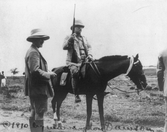 Roosevelt riding a horse and carrying a rifle