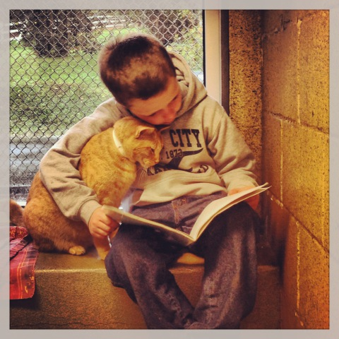Colby, one of the Book Buddies, and furry friend (Photo via Facebook)